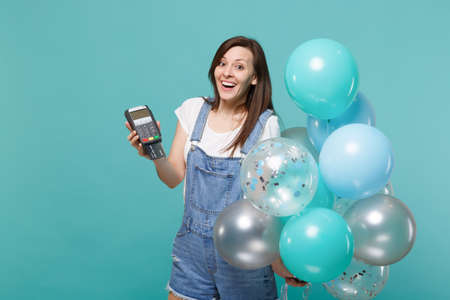 Excited woman hold wireless modern bank payment terminal to process, acquire credit card payments, colorful air balloons isolated on blue turquoise background. Birthday party, people emotions concept 写真素材