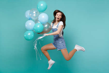 Amazed young woman in denim clothes keeping mouth open, jumping high, celebrating, holding colorful air balloons isolated on blue turquoise background. Birthday holiday party, people emotions concept