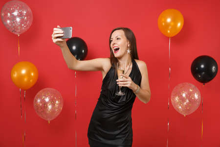 Excited young woman in black dress holding glass of champagne, doing taking selfie shot on mobile phone on bright red background air balloons. Happy New Year, birthday mockup holiday party concept