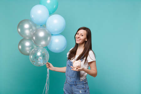 Portrait of smiling young woman in denim clothes holding piggy money bank celebrating with colorful air balloons isolated on blue turquoise background. Birthday holiday party, people emotions concept
