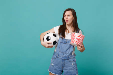 Puzzled young girl football fan watching match support favorite team with soccer ball, bucket of popcorn isolated on blue turquoise background. People emotions, sport family leisure lifestyle concept
