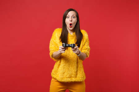 Amazed young woman in yellow fur sweater keeping mouth open, playing video game with joystick isolated on bright red wall background. People sincere emotions, lifestyle concept. Mock up copy space