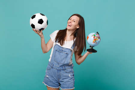 Laughing young woman football fan cheer up support favorite team with soccer ball, world globe isolated on blue turquoise background. People emotions, sport family leisure concept. Mock up copy space