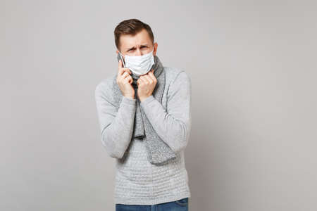 Crying dissatisfied young man in gray sweater, scarf sterile face mask talking on mobile phone isolated on grey background. Health, ill sick disease treatment, cold season concept. Mock up copy space Stockfoto