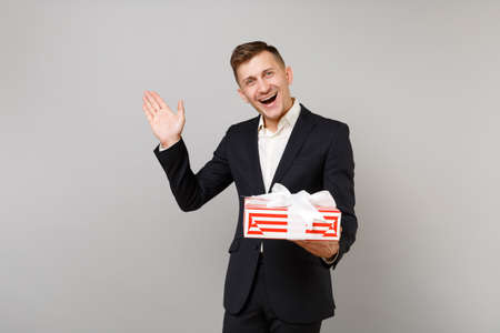 Cheerful business man waving, greeting with hand holding red striped present box with gift ribbon isolated on grey background. Achievement career wealth business. Women's Day birthday holiday concept 版權商用圖片