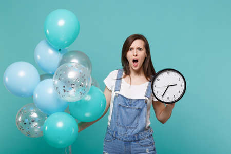 Shocked irritated young woman with opened mouth holding round clock while celebrating with colorful air balloons isolated on blue turquoise background. Birthday holiday party, people emotions concept
