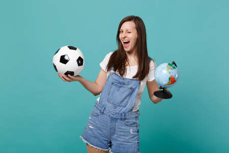 Funny woman football fan cheer up support favorite team with soccer ball, Earth world globe isolated on blue turquoise background. People emotions, sport family leisure concept. Mock up copy space