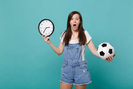 Bewildered young woman football fan holding soccer ball, round clock isolated on blue turquoise wall background in studio. Time is running out. People emotions, sport family leisure lifestyle concept