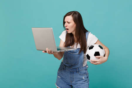 Perplexed young woman football fan holding soccer ball using laptop pc computer isolated on blue turquoise wall background. People emotions, sport family leisure lifestyle concept. Mock up copy space