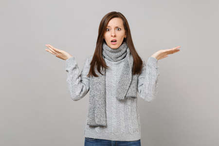 Shocked puzzled young woman in gray sweater scarf spreading hands isolated on grey wall background in studio. Healthy fashion lifestyle people sincere emotions cold season concept. Mock up copy space