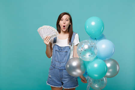 Amazed young woman holding fan of money in dollar banknotes cash money, celebrating with colorful air balloons isolated on blue turquoise background. Birthday holiday party, people emotions concept