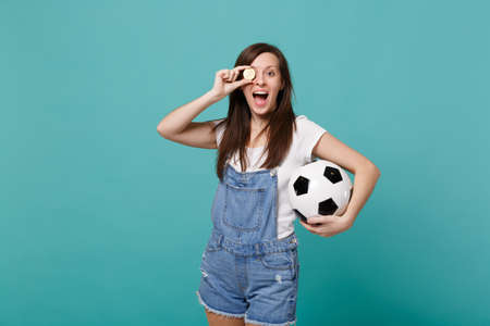 Cheerful young girl football fan support favorite team with soccer ball, covering eye with bitcoin future currency isolated on blue turquoise background. People emotions, sport family leisure concept