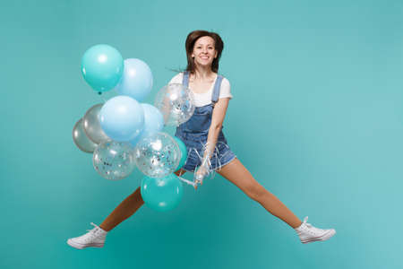 Portrait of smiling young woman in denim clothes jumping high, celebrating and holding colorful air balloons isolated on blue turquoise background. Birthday holiday party, people emotions concept Stock Photo