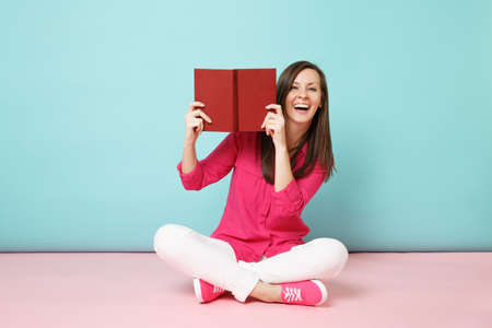Full length portrait of smiling woman in rose shirt blouse, white pants sit on floor read book isolated on pink blue pastel wall background studio. Fashion lifestyle concept. Mock up copy space Archivio Fotografico