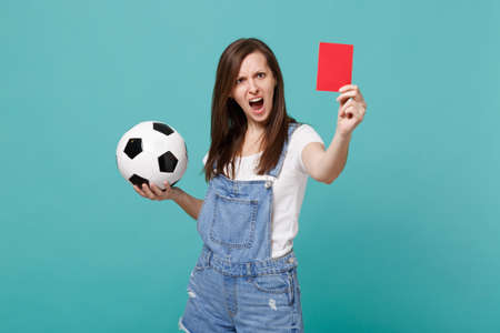 Angry irritated young woman football fan support team with soccer ball, red card, propose player retire from field isolated on blue turquoise background. People emotions, sport family leisure concept