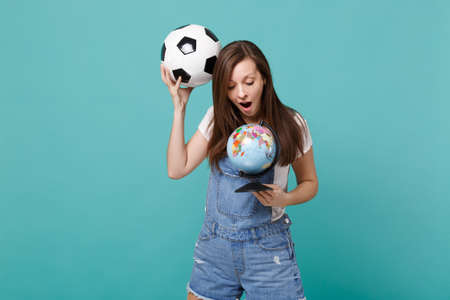Amazed young woman football fan holding soccer ball, looking on Earth world globe isolated on blue turquoise background. People emotions, sport family leisure lifestyle concept. Mock up copy space