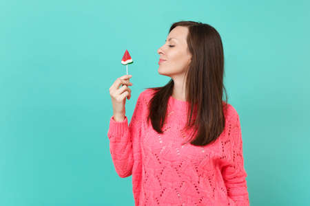 Pretty young woman in knitted pink sweater looking aside, holding in hand watermelon lollipop isolated on blue turquoise wall background, studio portrait. People lifestyle concept. Mock up copy space