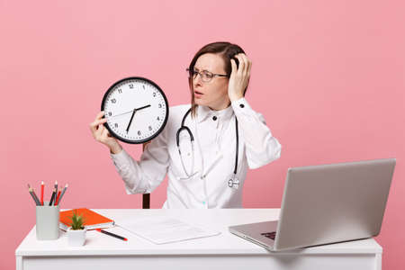 Female doctor sit at desk work on computer with medical document hold clock in hospital isolated on pastel pink wall background. Woman in medical gown glasses stethoscope. Healthcare medicine concept Banque d'images - 117123506