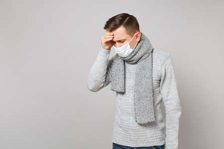 man in gray sweater scarf sterile face mask with lowered head putting hands forehead isolated on grey background. Healthy lifestyle, ill sick disease treatment, cold season concept. Mock up copy space Фото со стока