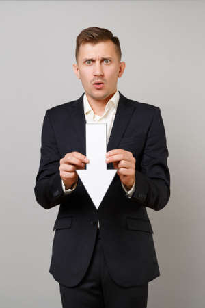 Shocked concerned young business man in classic black suit, shirt holding down value fall arrow isolated on grey background in studio. Achievement career wealth business concept. Mock up copy space
