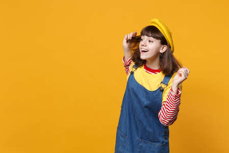 Curious girl teenager in french beret, denim sundress looking aside attentively far away distance isolated on yellow wall background. People sincere emotions, lifestyle concept. Mock up copy space