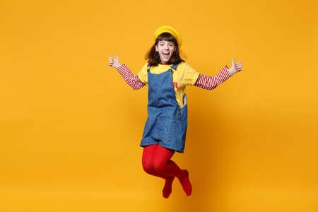 フランスのベレーで笑う女の子のティーンエイジャー、親指を示すデニムサンドレスは、ジャンプアップし、スタジオで黄色の壁の背景に孤立して浮気。人々はライフスタイルの概念に感情を与えます。コピースペースをモックアップ