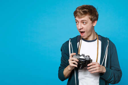 Amazed young man in casual clothes keeping mouth wide open looking aside holding retro vintage photo camera isolated on blue background. People sincere emotions, lifestyle concept. Mock up copy space