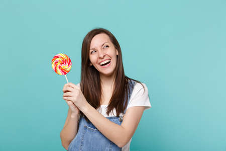 Portrait of laughing attractive young woman in denim clothes looking up, holding colorful round lollipop isolated on blue turquoise background in studio. People lifestyle concept. Mock up copy space