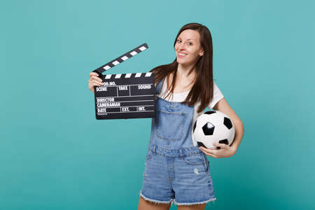 Beautiful young woman football fan support favorite team with soccer ball, classic black film making clapperboard isolated on blue turquoise background. People emotions, sport family leisure concept