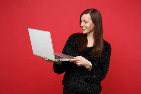 Portrait of smiling young woman in black fur sweater working on laptop pc computer isolated on bright red wall background in studio. People sincere emotions, lifestyle concept. Mock up copy space