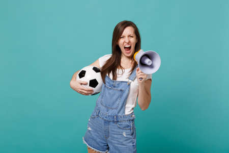 Crazy woman football fan scream in megaphone, support favorite team with soccer ball isolated on blue turquoise background. People emotions, sport family leisure lifestyle concept. Mock up copy space