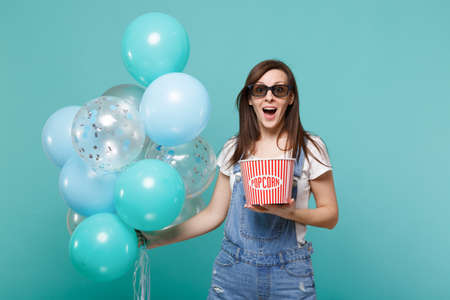 Amazed woman in 3d glasses watching movie film, hold bucket of popcorn celebrating with colorful air balloons isolated on blue turquoise background. Birthday holiday party, emotions in cinema concept