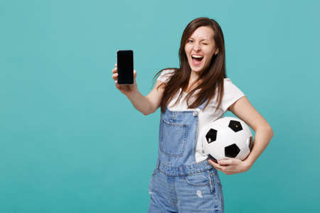 Cheerful blinking woman football fan holding soccer ball, mobile phone with blank empty screen isolated on blue turquoise background. People emotions, sport family leisure concept. Mock up copy space Reklamní fotografie - 117332249
