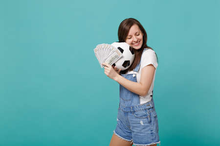 Tender young girl football fan with closed eyes support favorite team with soccer ball, fan of money in dollar banknotes cash money isolated on blue turquoise background. Sport family leisure concept