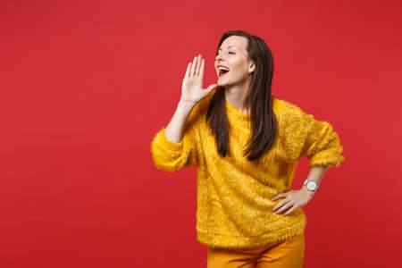 Portrait of young woman in yellow fur sweater looking aside speaking with hand gesture isolated on bright red wall background in studio. People sincere emotions, lifestyle concept. Mock up copy space Banco de Imagens