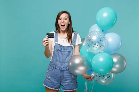 Shocked young woman keeping mouth wide open holding credit bank card celebrating with colorful air balloons isolated on blue turquoise wall background. Birthday holiday party, people emotions concept