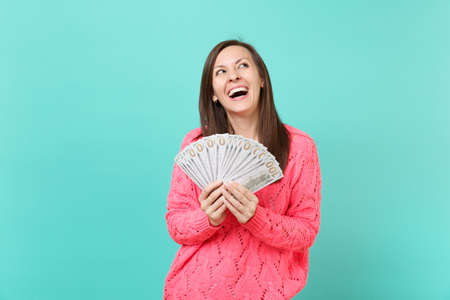 Laughing young girl in knitted pink sweater looking up hold in hand lots bunch of dollars banknotes cash money isolated on blue wall background in studio. People lifestyle concept. Mock up copy space Stock Photo - 117332656