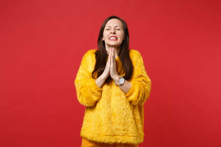 Pleading young woman in yellow fur sweater with closed eyes folded her hands, praying isolated on bright red wall background in studio. People sincere emotions, lifestyle concept. Mock up copy space