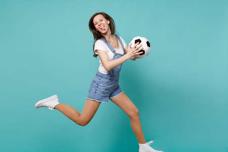 Funny woman football fan cheer up support favorite team holding soccer ball jumping isolated on blue turquoise background. People emotions, sport family leisure lifestyle concept. Mock up copy space