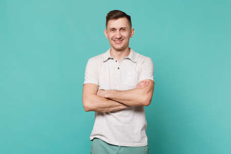Portrait of smiling young man in casual clothes standing and holding hands folded isolated on blue turquoise wall background in studio. People sincere emotions, lifestyle concept. Mock up copy space