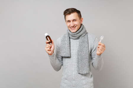 Smiling young man in gray sweater, scarf hold pour liquid medicine into bottle, spoon isolated on grey background. Healthy lifestyle ill sick disease treatment cold season concept. Mock up copy space Stock Photo