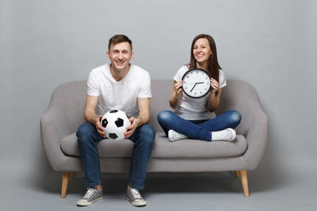 Fun couple woman man football fans in white t-shirt cheer up support favorite team with soccer ball holding round clock isolated on grey wall background. People sport family leisure lifestyle concept