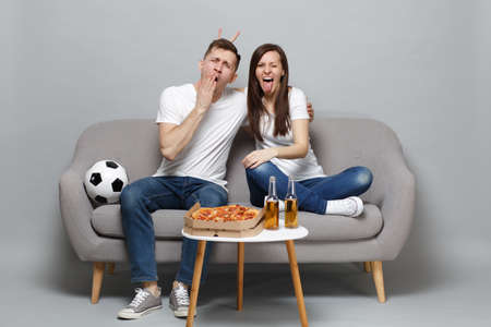 Crazy sleepy couple woman man football fans in white t-shirt cheer up support favorite team yawning showing tongue isolated on grey background. People emotions, sport family leisure lifestyle concept