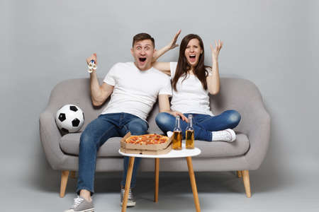 Screaming couple woman man football fans cheer up support favorite team with pipe, expressive gesticulating hands isolated on grey background. People emotions, sport family leisure lifestyle concept Banco de Imagens