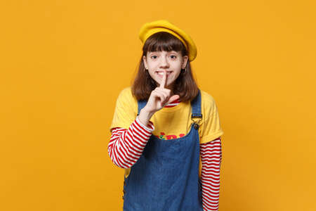Pretty girl teenager in french beret, denim sundress saying hush be quiet with finger on lips shhh gesture isolated on yellow background. People sincere emotions lifestyle concept. Mock up copy space