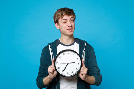 Portrait of funny young man in casual clothes blinking, holding round clock isolated on blue background in studio. Time is running out. People sincere emotions, lifestyle concept. Mock up copy space 版權商用圖片