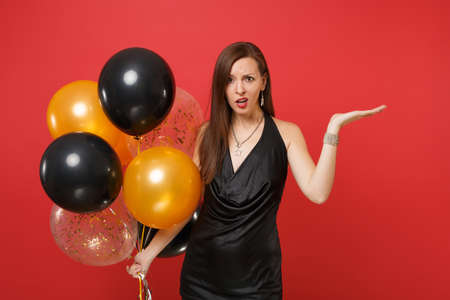 Bewildered young woman in little black dress celebrating pointing hands aside holding air balloons isolated on red background. St. Valentine's Day Happy New Year birthday mockup holiday party concept Stock fotó
