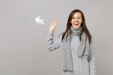 Happy young woman in gray sweater, scarf recovering and throwing paper napkin isolated on grey wall background. Healthy lifestyle, ill sick disease treatment, cold season concept. Mock up copy space