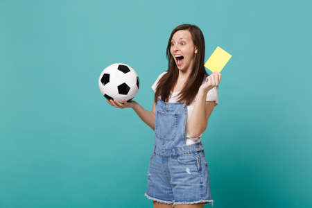 Excited screaming woman football fan support team with soccer ball, yellow card, propose player retire from field isolated on blue turquoise background. People emotions, sport family leisure concept