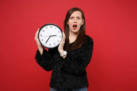 Portrait of shocked irritated young woman in black fur sweater holding round clock isolated on bright red wall background in studio. People sincere emotions, lifestyle concept. Time is running out Banque d'images - 117867139